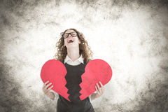 A Composite image of geeky hipster holding a broken heart card. Geeky hipster holding a broken heart card against grey background Stock Photos