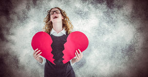 Composite image of geeky hipster holding a broken heart card Stock Image