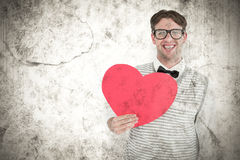 A Composite image of geeky hipster holding heart card Royalty Free Stock Images