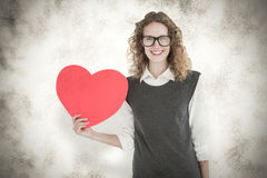 A Composite image of geeky hipster holding heart card Stock Photos