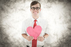 A Composite image of geeky hipster holding heart card Royalty Free Stock Image