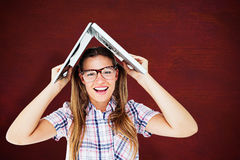 Composite image of geeky hipster holding her laptop over her head Stock Photography