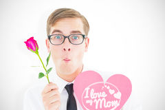 Composite image of geeky hipster holding a red rose and heart card Royalty Free Stock Images