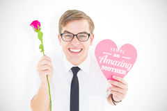 Composite image of geeky hipster holding a red rose and heart card. Geeky hipster holding a red rose and heart card against mothers day greeting Stock Images