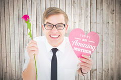 Composite image of geeky hipster holding a red rose and heart card Royalty Free Stock Photos