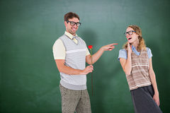 Composite image of geeky hipster holding rose and pointing his girlfriend Royalty Free Stock Image