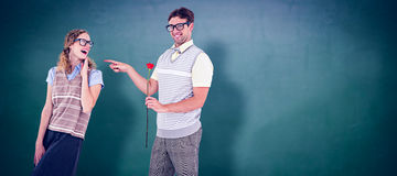 Composite image of geeky hipster holding rose and pointing his girlfriend Royalty Free Stock Photo