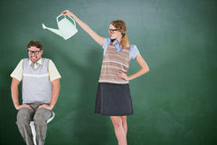 Composite image of geeky hipster holding watering can above her boyfriend Stock Image