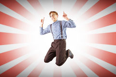 Composite image of geeky hipster jumping and pointing Royalty Free Stock Photography