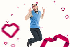Composite image of geeky hipster jumping and smiling. Geeky hipster jumping and smiling against hearts Stock Photography