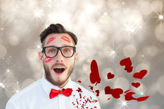 Composite image of geeky hipster with kisses on his face Stock Image