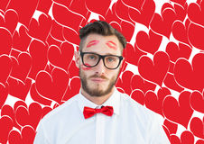 Composite image of geeky hipster with kisses on his face Stock Photo