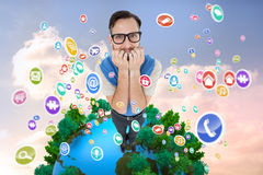 Composite image of geeky hipster looking nervously at camera Stock Photo
