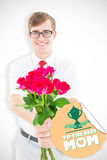 Composite image of geeky hipster offering bunch of roses Stock Photo