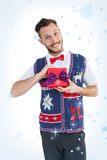 Composite image of geeky hipster offering christmas gift Royalty Free Stock Photo