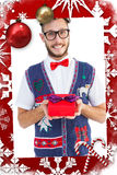 Composite image of geeky hipster offering christmas gift Stock Photos