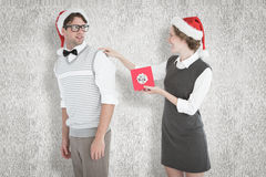 A Composite image of geeky hipster offering present to her boyfriend Stock Photo