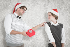 A Composite image of geeky hipster offering present to his girlfriend Royalty Free Stock Photo