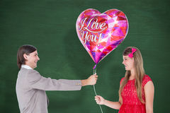 A Composite image of geeky hipster offering red heart shape balloon to his girlfriend Royalty Free Stock Photos