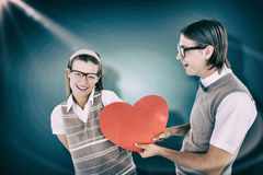 Composite image of geeky hipster offering red heart to his girlfriend Stock Photo