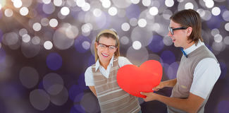 Composite image of geeky hipster offering red heart to his girlfriend Stock Images