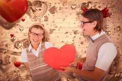 Composite image of geeky hipster offering red heart to his girlfriend Stock Image