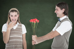 A Composite image of geeky hipster offering red roses to his girlfriend Royalty Free Stock Images