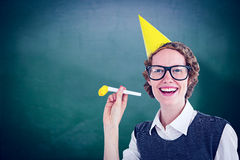 Composite image of geeky hipster in party hat with horn Stock Image