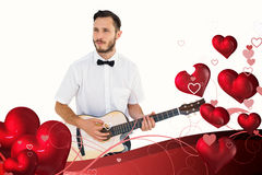 Composite image of geeky hipster playing the guitar. Geeky hipster playing the guitar  against valentines heart design Royalty Free Stock Images