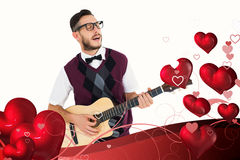 Composite image of geeky hipster playing guitar and singing. Geeky hipster playing guitar and singing against valentines heart design Stock Photo