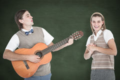 A Composite image of geeky hipster serenading his girlfriend with guitar Royalty Free Stock Images