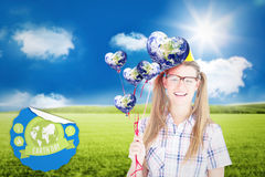 Composite image of geeky hipster smiling at camera and holding red balloons Royalty Free Stock Image