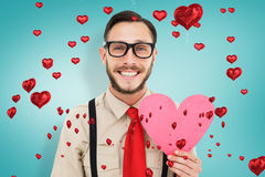 Composite image of geeky hipster smiling and holding heart card. Geeky hipster smiling and holding heart card against blue vignette background royalty free stock photography