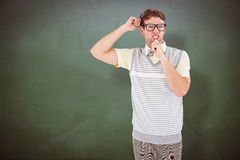 Composite image of geeky hipster thinking with hand on chin Royalty Free Stock Photo