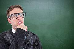 Composite image of geeky hipster thinking with hand on chin Royalty Free Stock Images