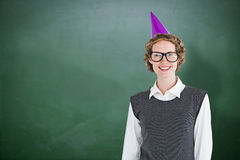 Composite image of geeky hipster wearing a party hat Royalty Free Stock Images