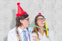 A Composite image of geeky hipster wearing a party hat with blowing party horn Stock Photos