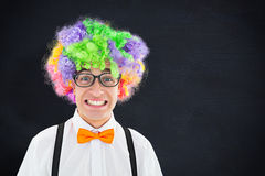 Composite image of geeky hipster wearing a rainbow wig. Geeky hipster wearing a rainbow wig against blackboard Stock Photos
