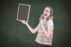 A Composite image of geeky hipster woman holding blackboard and singing into microphone Stock Photo