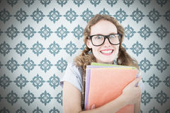 Composite image of geeky hipster woman holding files. Geeky hipster woman holding files  against blue background Stock Images