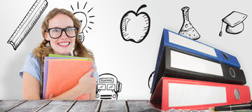 Composite image of geeky hipster woman holding files. Geeky hipster woman holding files  against desk Stock Images