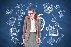 Composite image of geeky hipster woman looking nervous. Geeky hipster woman looking nervous against blue chalkboard Stock Photo