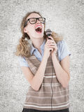 A Composite image of geeky hipster woman singing into a microphone Royalty Free Stock Images
