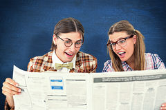 Composite image of geeky hipsters reading the newspaper Stock Image