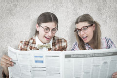 A Composite image of geeky hipsters reading the newspaper Royalty Free Stock Photography