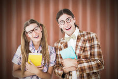 Composite image of geeky hipsters smiling at camera Royalty Free Stock Image