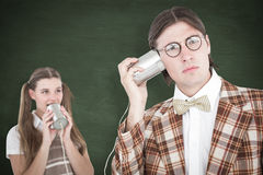 A Composite image of geeky hipsters using string phone Stock Photo