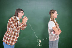 Composite image of geeky hipsters using string phone Stock Image