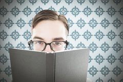 Composite image of geeky man looking over book Royalty Free Stock Photos