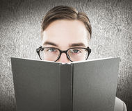 Composite image of geeky man looking over book Royalty Free Stock Images